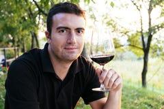 Man som dricker vin Arkivbild