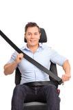 Man som fäster hans säkerhetsbälte på ett bilsäte arkivfoto