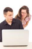 Man som fångas i handlingen av fusket över internet på datoren Arkivbild