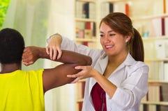 Man som får fysisk armbehandling från den physio terapeut, henne händer som arbetar på hans skuldra och armbågen, medicinskt begr arkivbilder