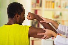 Man som får fysisk armbehandling från den physio terapeut, henne händer som arbetar på hans skuldra och armbågen, medicinskt begr royaltyfri foto