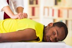 Man som får fysisk behandling från den physio terapeuten, henne händer som arbetar på hans baksida och applicerar massagen, läkar arkivbild