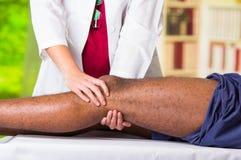 Man som får knäbehandling från den physio terapeuten, henne händer som rymmer hans ben och applicerar massagen, skadaläkarundersö fotografering för bildbyråer
