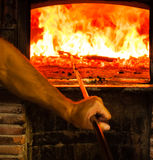 Man som förbereder den Wood ugnen för Pizza Royaltyfri Bild
