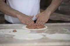 Man som förbereder Lahmacun deg med händer på kökskrivbordet Arkivbild
