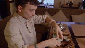 Man som förbereder traditionellt japanskt te på ceremoni för stund för temagasin arkivfilmer