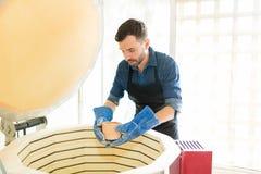 Man som förlägger den Clay Mug Into Kiln At krukmakeristudion arkivfoton