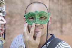 Man som försöker på en venetian karnevalmaskering Fotografering för Bildbyråer