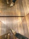 Man som försöker på trendiga skor och kontrollerar i spegeln arkivbild