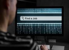 Man som finner för ett jobb på datoren royaltyfri fotografi