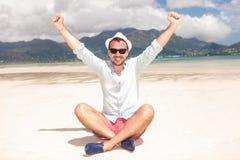 Man som firar framgång på stranden Arkivbild