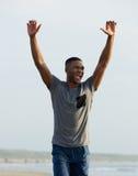 Man som firar med armar som lyfts upp Arkivfoto