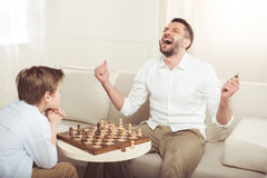 Man som firar seger i schacklek med den upprivna sonen Royaltyfri Bild