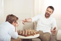 Man som firar seger i schacklek och pekar på den upprivna sonen Arkivfoto