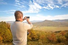 Man som fotograferas på en smartphone Fotografering för Bildbyråer