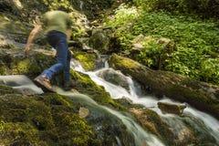 Man som fotvandrar över vattenfallet med rörelsesuddighet Arkivfoton