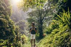 Man som fotvandrar i frodig rainforest Arkivfoton
