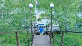 Man som fotvandrar i skogen, som han klättrar på trappan - loppet och att fotvandra En man som upp går trappan Royaltyfria Bilder