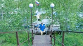 Man som fotvandrar i skogen, som han klättrar på trappan - loppet och att fotvandra En man som upp går trappan Arkivbild