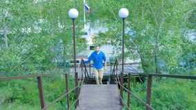 Man som fotvandrar i skogen, som han klättrar på trappan - loppet och att fotvandra En man som upp går trappan Arkivbilder