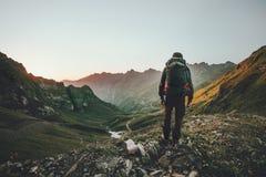 Man som fotvandrar på solnedgångberg med den tunga ryggsäcken fotografering för bildbyråer
