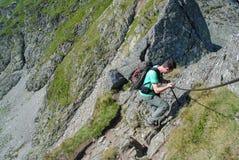 Man som fotvandrar på svår bergslinga fotografering för bildbyråer