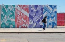 Man som framme går av väggen med grafitti Arkivfoton