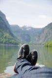 Man som framme ligger av en sjö Arkivfoto