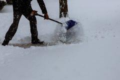 Man som framme skyfflar snö från trottoaren av hans hus efter en man för tungt snöfall som tar bort snö med en skyffel Arkivbild