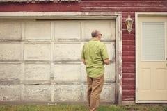 Man som framme står av ett ridit ut garage arkivbilder