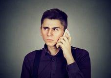 Man som frustreras av någon som lyssnar på mobiltelefonen royaltyfri fotografi