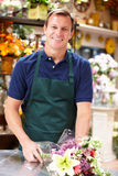Man som fungerar i blomsterhandlare Fotografering för Bildbyråer