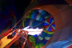 Man som fyller den orange ballongen med varm luft Arkivbild