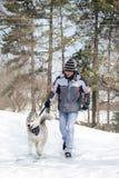 Man som går hans hund i snöig skog Fotografering för Bildbyråer