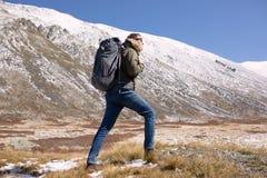 Man som går i bergen med en ryggsäck royaltyfri fotografi
