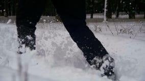 Man som går i det djupa insnöat vinterskogen på den snöig dagen långsam rörelse stock video