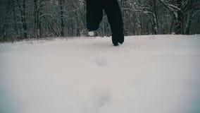 Man som går i det djupa insnöat vinterskogen på den snöig dagen långsam rörelse lager videofilmer