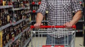 Man som går med en shoppa vagn på supermarket lager videofilmer