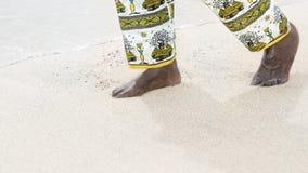 Man som går på en vit sandstrand Royaltyfria Foton