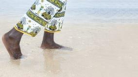 Man som går på en vit sandstrand Royaltyfria Bilder