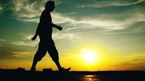 Man som går på gatan i solnedgång arkivfilmer