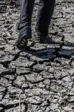 Man som går på sprucken ökenjordekologi Arkivbild