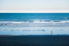 Man som går på stranden Arkivfoto