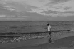 Man som går på stranden och talar på telefonen royaltyfri foto