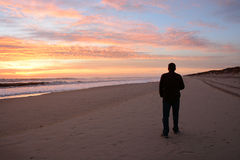 Man som går på stranden på härlig soluppgång arkivfoton