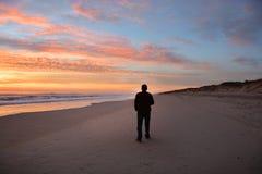 Man som går på stranden på härlig soluppgång royaltyfri bild