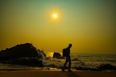 Man som går på tid för strandmorgonsoluppgång arkivbild