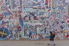 Man som går passerandet ett enormt konstverk på 798 Art Zone i Peking Royaltyfri Foto