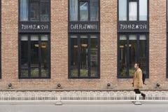Man som går passerandet ett kafé på 798 Art Zone i Peking Arkivfoto