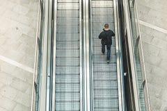 Man som går runt om att se hans mobiltelefon Man som klättrar rulltrappan royaltyfri foto